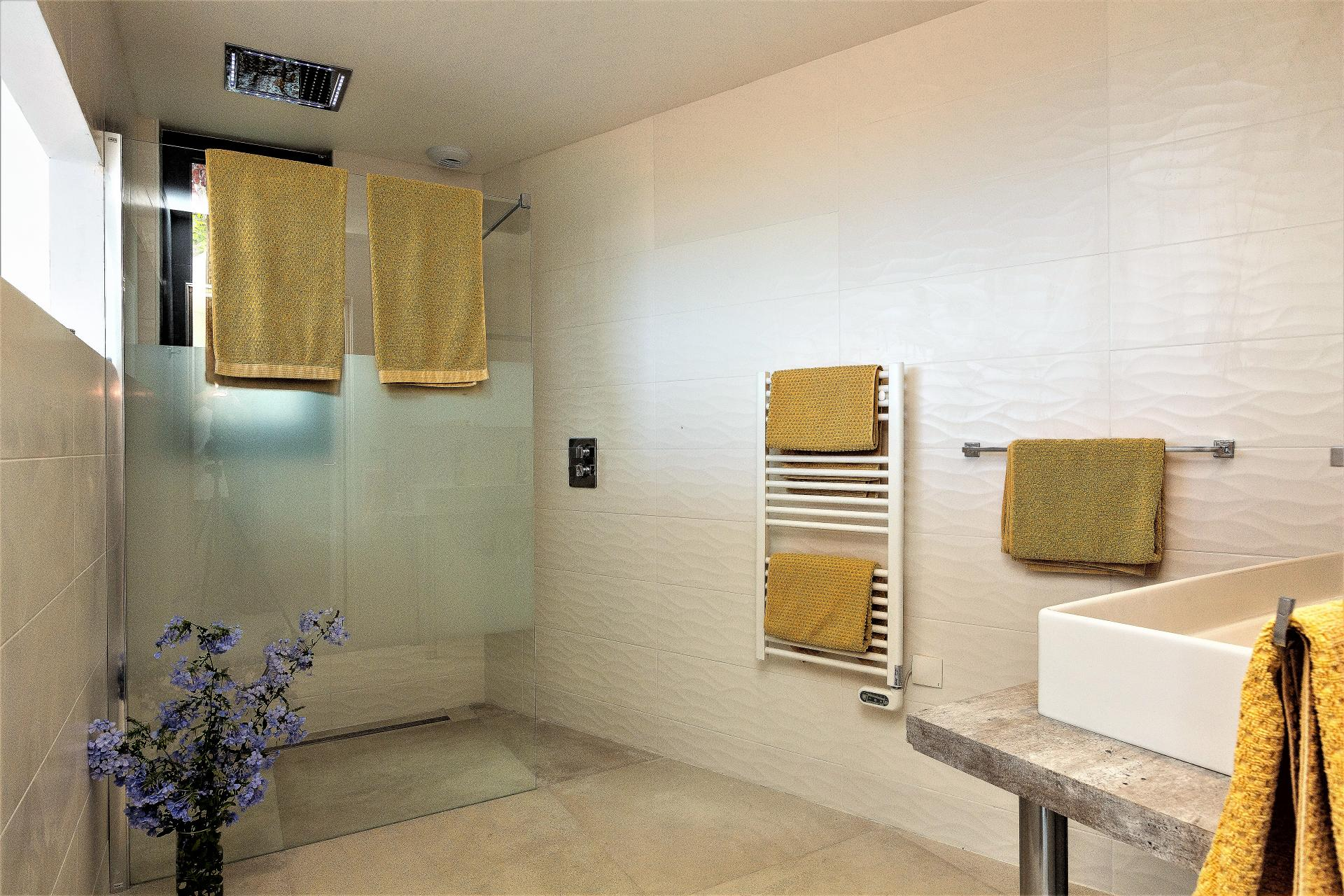 A BATHROOM WITH WALKING SHOWER IN VILLA INFINITY